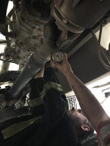 Worker performing hydraulic system repair